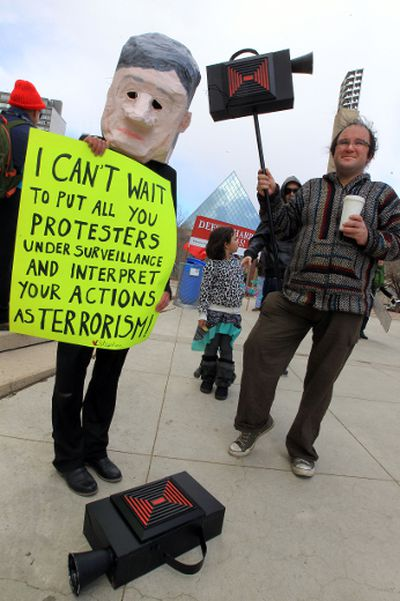 Stuart Andrews (r) carries a fake camera during a Bill C-51 protest at Churchill Square in Edmonton, Alta. on Saturday April 18, 2015. Perry Mah/Edmonton Sun/Postmedia Network