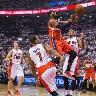 Toronto Raptors Kyle Lowry with DeMar DeRozan and Washington Wizards  John Wall in Game 1 during 1st half playoff  action  at the Air Canada Centre in Toronto, Ont. on Saturday April 18, 2015. Ernest Doroszuk/Toronto Sun/Postmedia Network