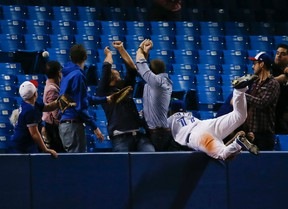 Blue Jays outfielder Kevin Pillar dives into the stands after a foul ball in the eighth inning of a game on April 14, 2015 at the Rogers Centre. (STAN BEHAL/Toronto Sun)