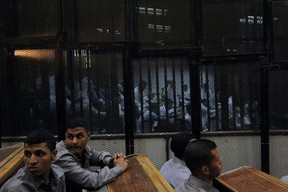 Egyptian defendants sit behind bars during their trial at a police institute in the outskirts of Cairo on April 19, 2015. An Egyptian court sentenced 11 football fans to death after a retrial over a 2012 stadium riot in the canal city of Port Said that left 74 people dead. AFP PHOTO / STR