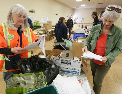 Lindy Iversen, an organizer of the Re-Use & Eco-Fair, left, and volunteer Dorothy Embacher refer to want lists, from groups and organizations looking for specific items, as they sort through donated articles dropped off at the Meaford and St. Vincent Community Centre Saturday. (James Masters/Owen Sound Sun Times)
