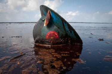 A hard hat from an oil worker lies in oil from the Deepwater Horizon oil spill on East Grand Terre Island, Louisiana, in this file photo taken June 8, 2010.   REUTERS/Lee Celano