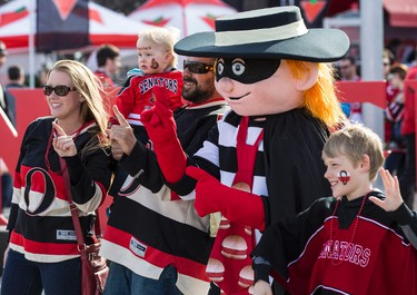 """Ottawa Senators fans pose with a mascot of the  """"Hamburglar"""", the nickname of Sens goaltender Andrew Hammond, in the Red Zone outside of the Canadian Tire Centre in Ottawa before game three of the first round playoff series between the Ottawa Senators and Montreal Canadiens on Sunday April 19, 2015. Errol McGihon/Ottawa Sun/Postmedia Network"""