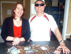 The Salvation Army's Gerri St. Pierre accepts a donation of coins and bills from Jim Aubie. Aubie collected the money over the past 15 years as a Wallaceburg postman, as he looked for money on the ground as he walked along his route every day. He retired on April 1 and donated the found money to the Salvation Army's office in Wallaceburg. DAVID GOUGH/ POSTMEDIA NETWORK
