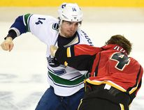 Canucks forward Alex Burrows fights Calgary's Kris Russell in Game 3 at the Scotiabank Saddledome. CALGARY SUN