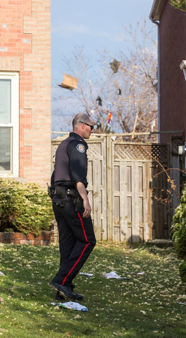 A police officer among the debris on the ground and a tree after a reported house collapse near Brimley Rd and Steeles Ave E in Toronto, Ont. on Monday April 20, 2015. Ernest Doroszuk/Toronto Sun/Postmedia Network