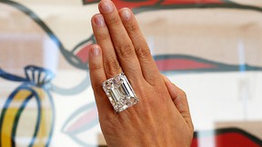 """A woman displays a 100.20-carat diamond ring in front of Roy Lichtenstein's 1962 painting """"The Ring (Engagement)"""" at a pre-auction viewing at Sotheby's in Los Angeles, Calif., in this file photo taken March 25, 2015. (REUTERS/Lucy Nicholson/Files)"""