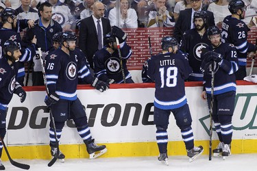 WINNIPEG, MB - APRIL 22: (L-R) Chris Thorburn #22, Andrew Ladd #16, Bryan Little #18 and Drew Stafford #12 of the Winnipeg Jets stand by the bench during a break in third period action in Game Four of the Western Conference Quarterfinals against the Anaheim Ducks during the 2015 NHL Stanley Cup Playoffs at the MTS Centre on April 22, 2015 in Winnipeg, Manitoba, Canada.   Marianne Helm/Getty Images/AFP == FOR NEWSPAPERS, INTERNET, TELCOS & TELEVISION USE ONLY ==