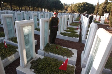 A New Zealand soldier looks at the tombstones of Turkish soldiers at the Turkish memorial marking the 100th anniversary of the Battle of Canakkale, as part of the Gallipoli campaign in Gallipoli March 18, 2015. Turkish jets flew overhead and warships cut through rough waters in the Dardanelles Straits on Wednesday to mark the centenary of one of the Ottoman Empire's final victories, as fascination with the imperial past flourishes under President Tayyip Erdogan. Record numbers of Turks have flocked to these headlands in recent years to pay homage to the defence of the Dardanelles during the Gallipoli campaign of World War One. REUTERS/Osman Orsal