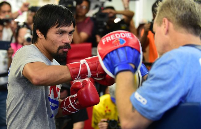 Manny Pacquiao (left) spars with his coach, Freddy Roach, ahead of his upcoming fight against Floyd Mayweather during a training session at the Wild Card Boxing Club in Hollywood April 15, 2015. (AFP PHOTO/FREDERIC J. BROWN)