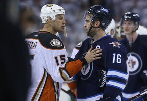 Winnipeg Jets captain Andrew Ladd (right) and Anaheim Ducks captain Ryan Getzlaf shake hands after the end of their NHL playoff series in Winnipeg on Wed., April 22, 2015. Kevin King/Winnipeg Sun/Postmedia Network
