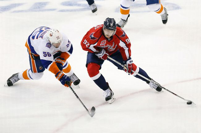 Washington Capitals centre Evgeny Kuznetsov skates with the puck around New York Islanders defenceman Johnny Boychuk en route to scoring a goal in the third period in Game 5 of the first round of the 2015 NHL playoffs at Verizon Center on April 23, 2015. (Geoff Burke/USA TODAY Sports)