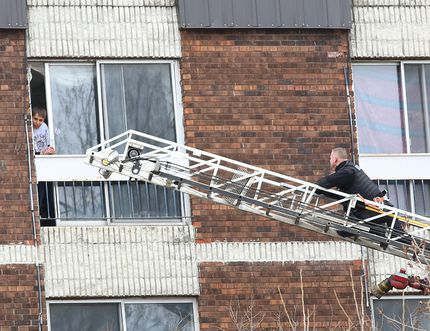 Police uses an aerial ladder to get closer to an apartment where a young man invol
