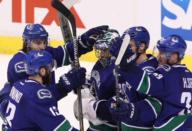 Vancouver Canucks' goalie Ryan Miller get congratulated by his teammates after beating the Calgary Flames 2-1 in Game 5  in Vancouver on Thursday. Photo by Carmine Marinelli/Postmedia Network.