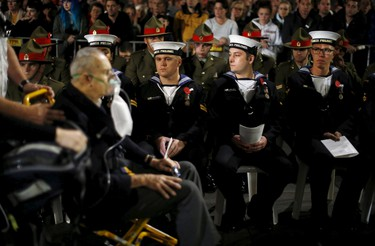 Sailors from New Zealand's Navy Base Philomel watch as a Cenotaph attendant is wheeled away by medical staff after collapsing during the dawn of ANZAC (Australian and New Zealand Army Corps) Day 100th anniversary commemoration at Sydney's Cenotaph in Australia, April 25, 2015. Commemorations on Turkey's Gallipoli peninsula on Friday marked the 100th anniversary of a World War One battle that helped shape the birth of new nations. Thousands of Australians and New Zealanders have flocked to the peninsula on Turkey's Aegean coast to remember the fallen in an ill-fated Allied campaign a century ago that claimed more than 130,000 lives. REUTERS/Jason Reed