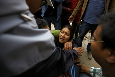 A woman cries as her son was trapped inside a collapsed house after an earthquake hit, in Kathmandu, Nepal April 25, 2015. REUTERS/Navesh Chitrakar