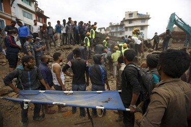 Rescue workers search for bodies as a stretcher is kept ready after an earthquake hit, in Kathmandu, Nepal April 25, 2015. REUTERS/Navesh Chitrakar
