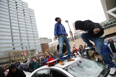 """Protesters jump on a police car at a rally to protest the death of Freddie Gray who died following an arrest in Baltimore, Maryland April 25, 2015. More than 1,000 demonstrators chanting """"shut it down"""" marched through Baltimore on Saturday to protest the death of a black man who died after being taken into police custody. REUTERS/Shannon Stapleton"""