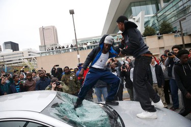 """Protesters jump on a car at a rally to protest the death of Freddie Gray who died following an arrest in Baltimore, Maryland April 25, 2015. More than 1,000 demonstrators chanting """"shut it down"""" marched through Baltimore on Saturday to protest the death of a black man who died after being taken into police custody. REUTERS/Shannon Stapleton"""