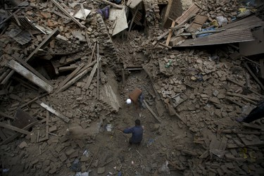 People search for family members trapped inside collapsed houses a day after an earthquake in Bhaktapur, Nepal April 26, 2015. Rescuers dug with their bare hands and bodies piled up in Nepal on Sunday after an earthquake devastated the heavily crowded Kathmandu valley, killing at least 1,900, and triggered a deadly avalanche on Mount Everest.  REUTERS/Navesh Chitrakar      TPX IMAGES OF THE DAY