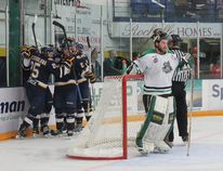 The Fort McMurray Oil Barons celebrate together after scoring their first goal of the game while Portage Terriers goaltender Justin Laforest looks on in Fort McMurray Alta. on Saturday April 25, 2015. The MOB beat the Terriers 3-1 to open the 2015 Crescent Point Energy Western Canada Cup. (Robert Murray/Fort McMurray Today/Postmedia Network)
