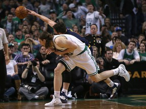 Kevin Love of the Cleveland Cavaliers reaches for a loss ball against Kelly Olynyk of the Boston Celtics in the first half in Game 4 during the first round of the 2015 NBA playoffs on April 26, 2015 at TD Garden. (Jim Rogash/Getty Images/AFP)