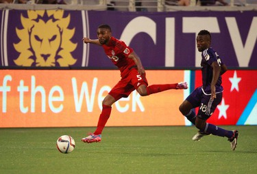 Apr 26, 2015; Orlando, FL, USA; Toronto FC defender Ashtone Morgan (5) passes the ball as Orlando City SC midfielder Kevin Molino (18) defends during the first half at Orlando Citrus Bowl Stadium.  Kim Klement-USA TODAY Sports