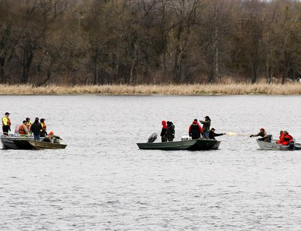 Members of Mohawk Fire Department, left, and local fishermen search for two missing boaters/fishermen Tyler Maracle and Matt Fairman on the Bay of Quinte between Deseronto, Ont. and Tyendinana Mohawk Territory, Ont, the day after the pair went missing, Monday, April 27, 2015. - Jerome Lessard/Belleville Intelligencer/Postmedia Network