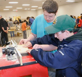 Ian Dufton (left), of St. Michael Catholic Secondary School, assists St. Columban student Ray Horan on the router machine on the woodworking station during the Huron-Perth Catholic District School Board's 5th annual Ontario Youth Apprenticeship Program (OYAP) Grade 7 technology days at the Mitchell & District Community Centre last Monday, April 20. ANDY BADER/MITCHELL ADVOCATE