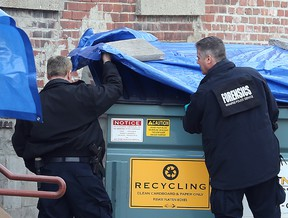Winnipeg police inspect several dumpsters behind Siloam Mission on Monday that is possibly connected to the murder of two homeless men over the weekend. (Brian Donogh/Winnipeg Sun)