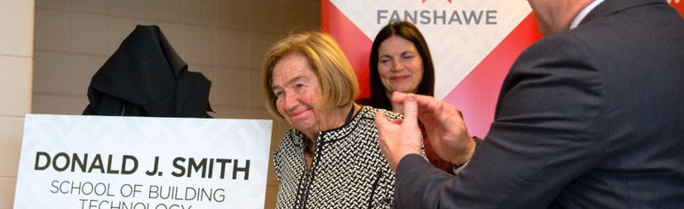 Joan Smith matriarch of the Smith clan, is applauded by Fanshawe President Peter Devlin after Smith spoke Monday during a ceremony to name the Fanshawe School of Building Technology after her late husband, Don Smith. (Mike Hensen/The London Free Press)