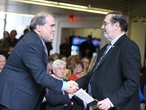 Gino Donato/The Sudbury Star   Leo Gerard, chair of the CROSH advisory board, right, shakes hands with with Dominic Giroux at the official opening of the CROSH centre for research in occupational safety and health at Laurentian University on Monday.