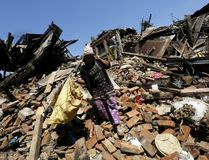 A woman carries her belongings as she walks over collapsed house after earthquake in Bhaktapur, Nepal April 27, 2015. Nepalese officials scrambled on Monday to get aid from the main airport to people left homeless and hungry by a devastating earthquake two days earlier, while thousands tired of waiting fled the capital Kathmandu for the surrounding plains. By afternoon, the death toll from Saturday's 7.9 magnitude earthquake had climbed to more than 4,000, and reports trickling in from remote areas suggested it would rise significantly. REUTERS/Adnan Abidi