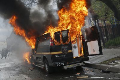 A Baltimore Metropolitan Police transport vehicle burns during clashes in Baltimore, Maryland April 27, 2015. Maryland Governor Larry Hogan declared a state of emergency and activated the National Guard to address the violence in Baltimore, his office said on Monday. Several Baltimore police officers were injured on Monday in violent clashes with young people after the funeral of a black man, Freddie Gray, who died in police custody, and local law enforcement warned of a threat by gangs. REUTERS/Shannon Stapleton
