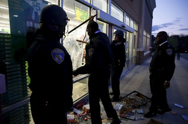 "Baltimore police officers arrive at a ""Deals"" store just vandalized and looted by rioters as darkness falls during clashes between rioters and police in Baltimore, Maryland April 27, 2015. Maryland Governor Larry Hogan declared a state of emergency and activated the National Guard to address the violence in Baltimore, his office said on Monday. Several Baltimore police officers were injured on Monday in violent clashes with young people after the funeral of a black man, Freddie Gray, who died in police custody, and local law enforcement warned of a threat by gangs.  REUTERS/Jim Bourg"