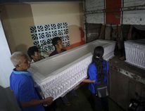 Workers load coffins from a church storage area ready to be taken to a police station in Cilacap, near the prison island of Nusakambangan, Central Java, Indonesia April 26, 2015 in this photo taken by Antara Foto. REUTERS/Idhad Zakaria/Antara Foto