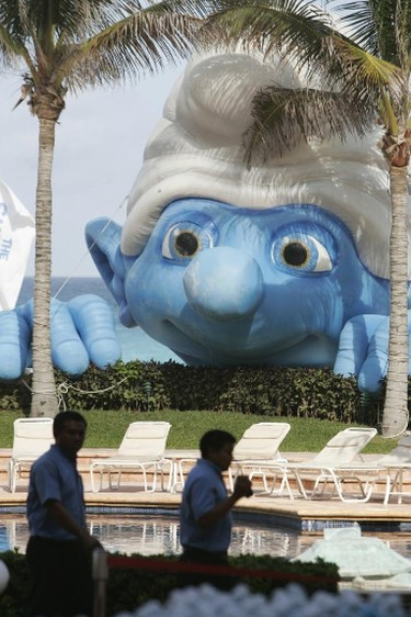 """Men walk in front of a giant inflatable Smurf during a photo-call for the film """"The Smurfs"""" in Cancun, Mexico July 10, 2011. REUTERS/Victor Ruiz Garcia"""