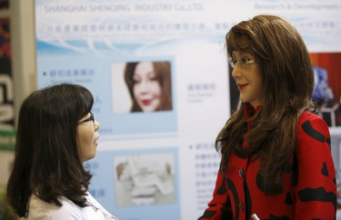 A woman looks at a humanoid robot named Yangyang (R) during its demonstration at the Global Mobile Internet Conference (GMIC) 2015 in Beijing, China, April 29, 2015.  REUTERS/Kim Kyung-Hoon