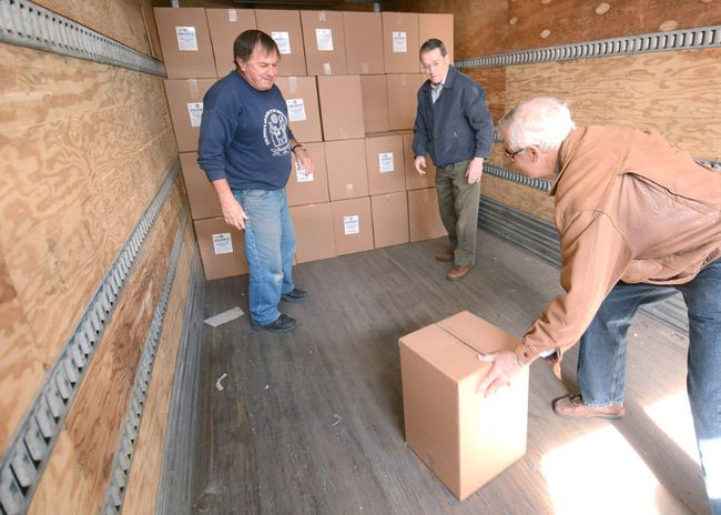 Rotary Club volunteers Stephen Chandler, Rheo Thompson and Ian MacLean, from left, load some of the hundreds of Aquaboxes for delivery to Nepal on Wednesday in Stratford. (SCOTT WISHART/The Beacon Herald)