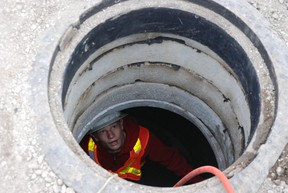 A sewer worker takes a camera inside a sewer main. (file photo)
