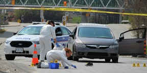Ottawa police crime scene investigators gather evidence, including swabs from the surface of Tremblay Rd. Sunday afternoon. A young man was gunned down around 8 a.m. A pair of shoes and a pillow lay next to a car, believed to be that of the victim -- a young Somali man who is survived by his parents and seven brothers. (DOUG HEMPSTEAD/Ottawa Sun)