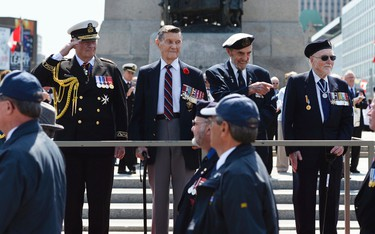 Gov. Gen. David Johnston (left) and three veterans look on as Veterans and Canadian Servicemen march by during the National Battle of the Atlantic parade and ceremony at the National War Memorial in Ottawa on Sunday, May 3, 2015. Matthew Usherwood/Ottawa Sun/Postmedia Networks