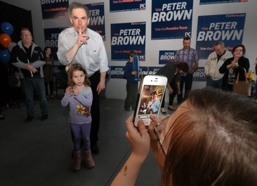 Alberta premier Jim Prentice is caught on the cell phone camera of five-year old photojournalist McKenzie Petrow as he asks the kids in the audience to be quiet while he speaks at PC candidate Peter Brown's campaign office in Airdrie, Ab., on Friday May 1, 2015. Danica Lumley, 4, had earlier joined him at centre stage. Mike Drew/Calgary Sun/Postmedia Network