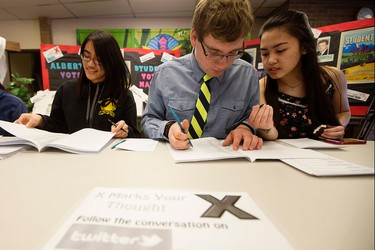 (left to right) Chief Electoral Officers Daphny Budaz, 17, Adam Lachacz, 17, and Angelina Salvador, 16, run the polling station during a mock provincial election at Holy Trinity High School, 7007 - 28 Avenue, in Edmonton, Alta. on Monday May 4, 2015. David Bloom/Edmonton Sun/Postmedia Network