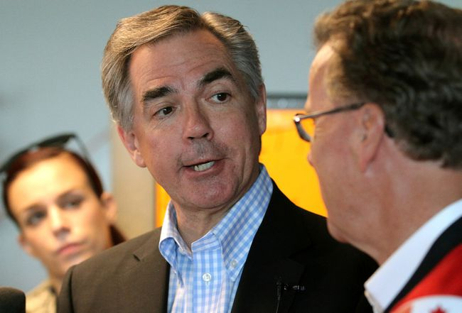 Alberta Premier Jim Prentice (L) chats with the media alongside PC Candidate Gordon Dirks at Dirks campaign office in Calgary, Alta. on Saturday May 2, 2015. Stuart Dryden/Calgary Sun