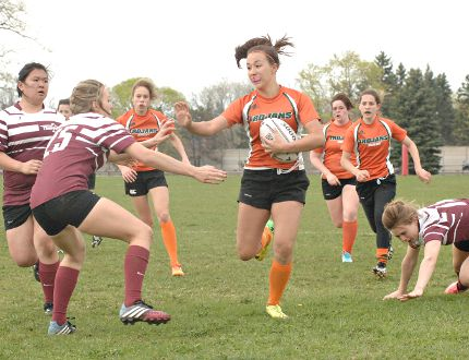 A North Park Collegiate ball carrier takes on a Pauline Johnson Collegiate defender during Brant County high school senior girls rugby action on Monday at Tollgate Tech. (Expositor Photo)