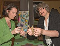 Jennifer Howes (left) of the Lansdowne Childrens' Centre gets pointers on making an origami paper crane from Charleen Rolston of the CMHA on Monday as Mental Health Week kicked off with a a gathering at the Polish Hall on Pearl Street. The crane is used by the American Foundation for Suicide Prevention as a symbol of prayer and peace for those living with mental illness. (BRIAN THOMPSON / The Expositor)