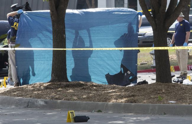 A tarpaulin is held up as the bodies of two gunmen are removed from behind a car during an investigation by the FBI and local police in Garland, Texas May 4, 2015. Texas police shot dead two gunmen who opened fire on Sunday outside an exhibit of caricatures of the Prophet Mohammad that was organized by a group described as anti-Islamic and billed as a free-speech event. REUTERS/Laura Buckman