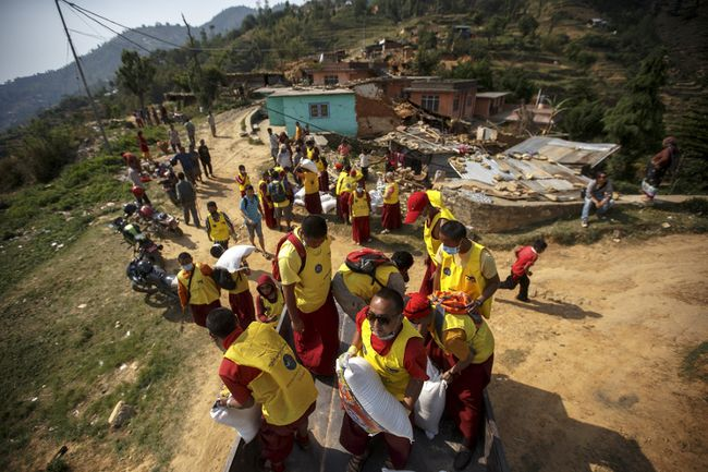 Nepali Buddhist monks from Benchen monastery unload relief supplies for earthquake victims as they arrive at Ramkot village on the outskirts of Kathmandu, Nepal, May 6, 2015. REUTERS/Athit Perawongmetha
