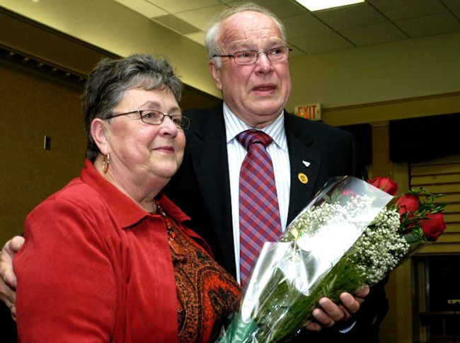 A tearful Bob Huskinson gives a bouquet to his wife, Janice, at his last city council meeting in this November 2006 file photo. (Ronald Zajac/Postmedia Network)